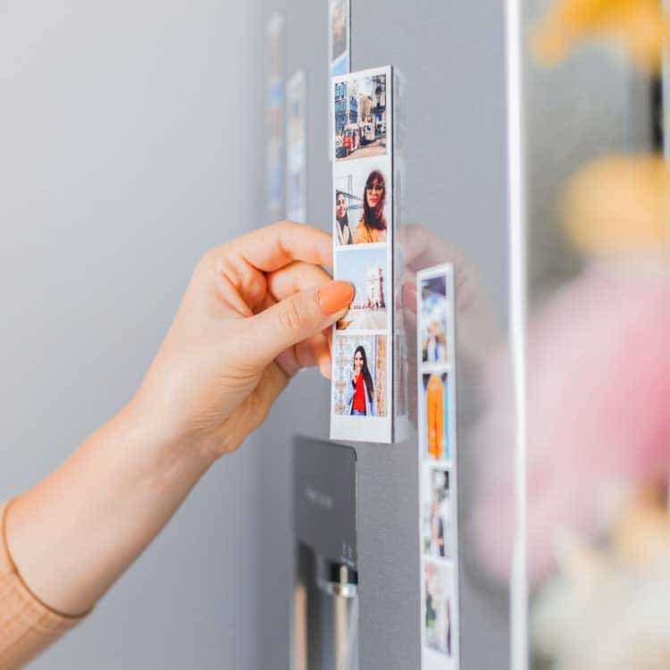 A woman sticking our photobooth print-out on her fridge. Our photo booth hire prices increase slightly for this feature